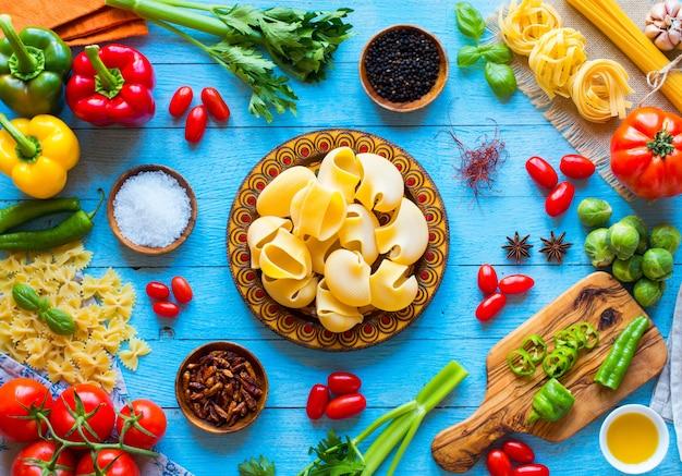 Vista superior de una mesa de madera llena de pastas italianas como pimientos, tomates, aceite de oliva, basi