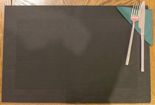 Vista superior de una mesa de madera y una servilleta de mimbre negro sobre la que se acuestan con un cuchillo y un tenedor