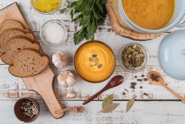 Vista superior mesa de madera con sopa y rebanadas de pan