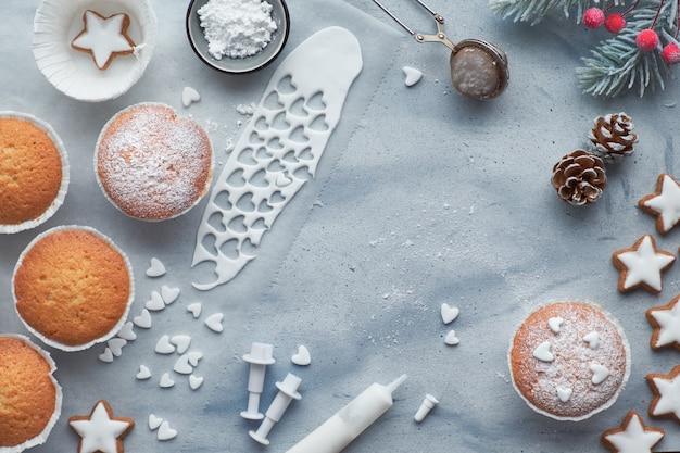 Vista superior de la mesa con magdalenas cubiertas de azúcar, glaseado de fondant y galletas de estrellas de navidad