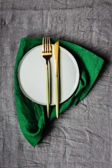 Vista superior de la mesa con mantel de lino gris, servilleta de lino verde, un plato blanco y elegante tenedor y cuchillo dorado