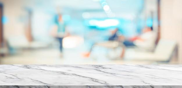 Vista superior de la mesa de mármol blanco vacío con paciente borrosa en el fondo del hospital