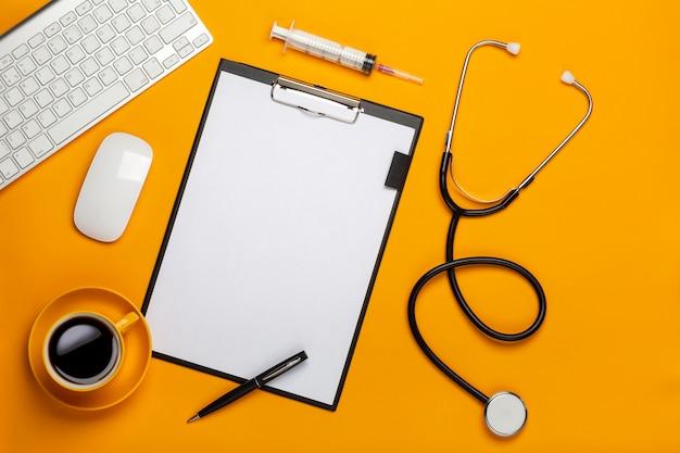 Vista superior de la mesa de un médico con estetoscopio, teclado, prescripción y píldoras, una taza de café sobre un fondo amarillo
