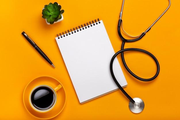 Vista superior de la mesa de un médico con libreta y estetoscopio, teclado, prescripción y píldoras.