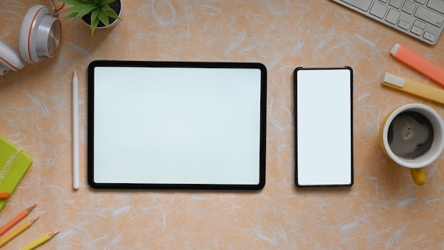 La vista superior de la mesa está rodeada por una tableta de computadora y varios equipos.
