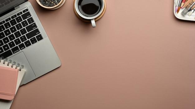 Vista superior de la mesa rosa con laptop, papelería y espacio para copiar en la sala de la oficina en casa