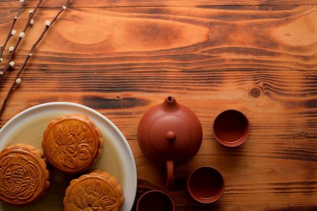 Vista superior de la mesa rústica con pasteles de luna tradicionales, juego de té y espacio para copiar. el carácter chino en el pastel de luna representa
