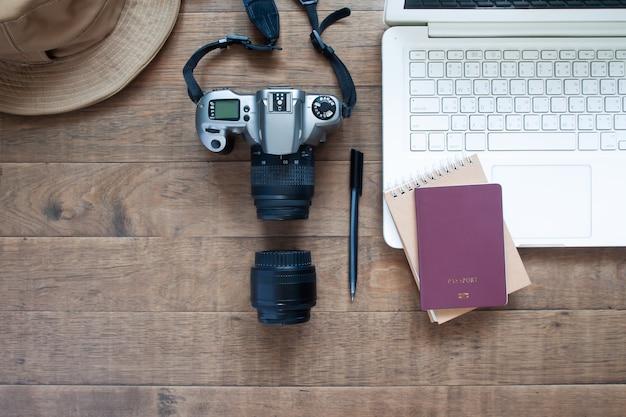 Vista superior de la mesa de trabajo de blogger con laptop, cámara y pasaporte.