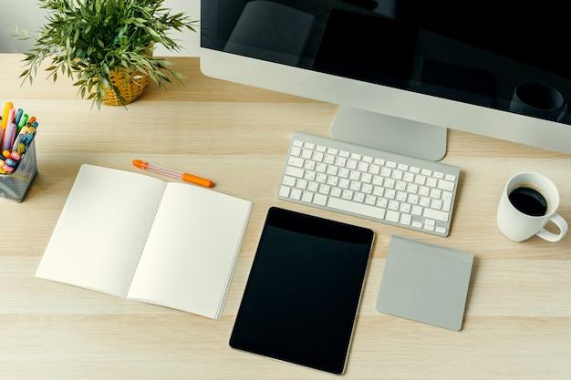 Vista superior de la mesa de trabajo con computadora, bloc de notas, taza de café y suministros