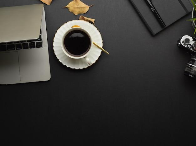 Vista superior de la mesa de trabajo con computadora portátil, taza de café, suministros y espacio para copiar en la sala de la oficina en casa