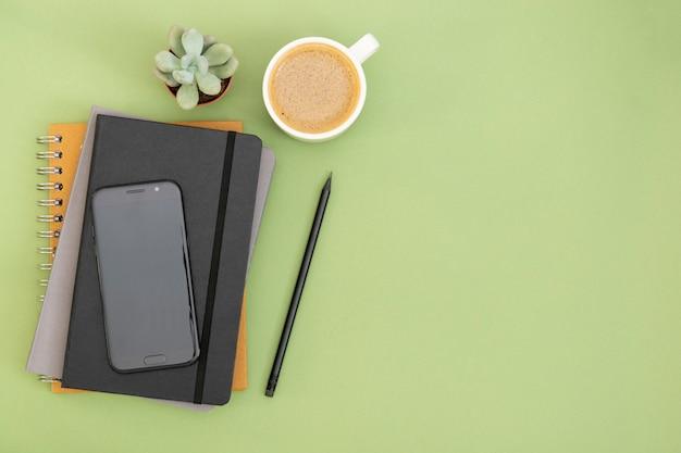 Vista superior de la mesa de trabajo. cuaderno cerrado negro, taza de café y teléfono inteligente. copiar espacio para texto. diseño simulado.