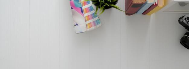 Vista superior de la mesa de trabajo mínima de diseño con muestra de color, libros, maceta y espacio de copia