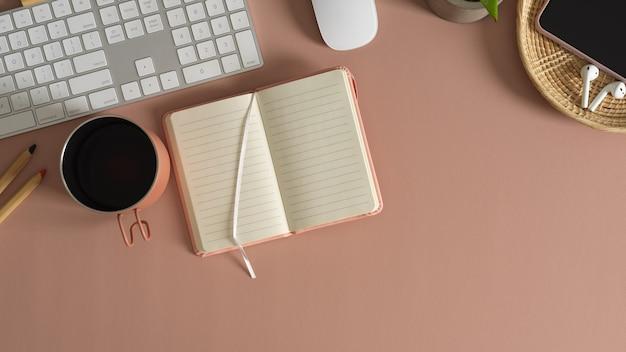 Vista superior de la mesa de trabajo moderna con cuaderno en blanco, taza de café y suministros de oficina sobre fondo de mesa rosa
