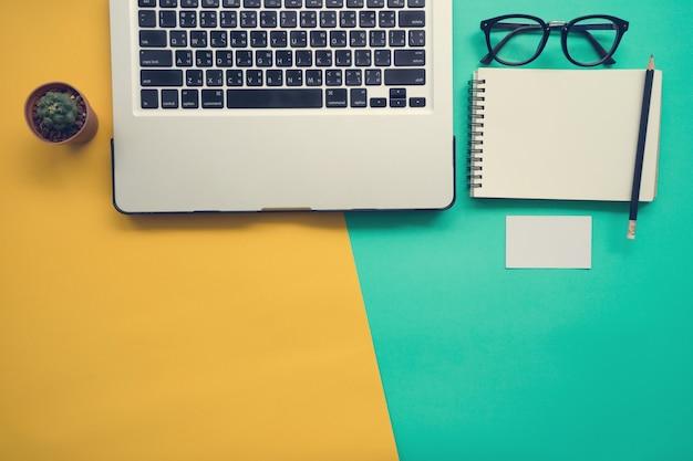 Vista superior de la mesa de trabajo con portátil portátil en blanco
