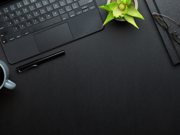 Vista superior de la mesa de trabajo con teclado de computadora portátil, bolígrafo, cuaderno, maceta y espacio para copiar en la sala de la oficina en casa
