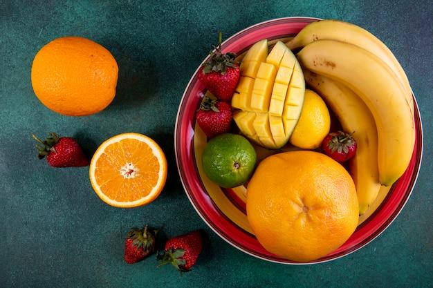 Vista superior mezcla de frutas en un plato de mango, fresa, lima y naranja sobre verde