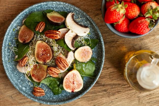 Vista superior mezcla de nueces e higos en un plato con fresas