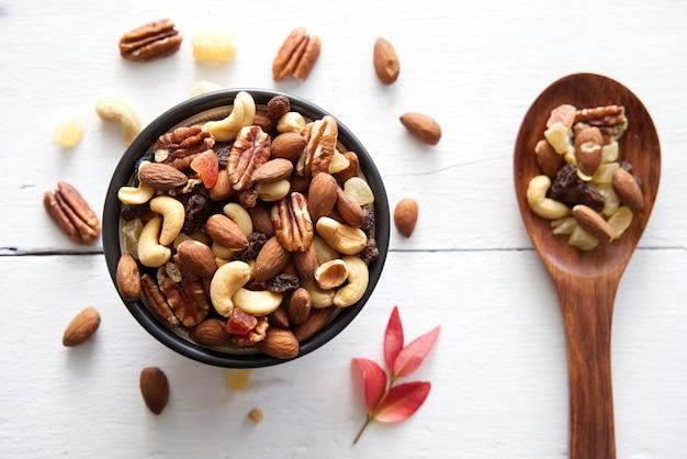Vista superior de la mezcla de nueces y frutos secos en el tazón y cuchara de madera.