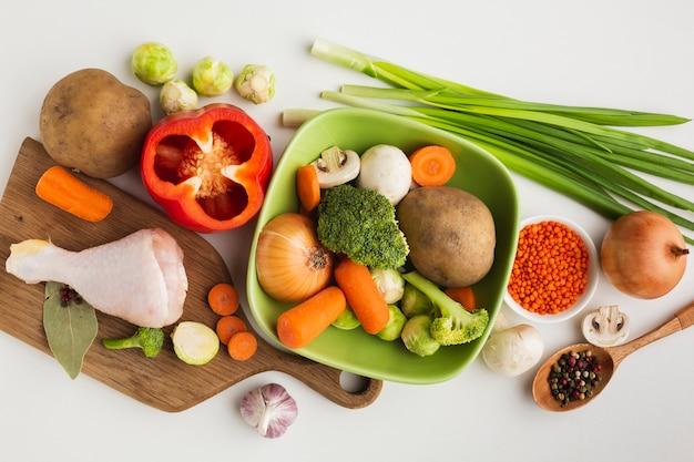 Vista superior mezcla de verduras en la tabla de cortar y en un tazón