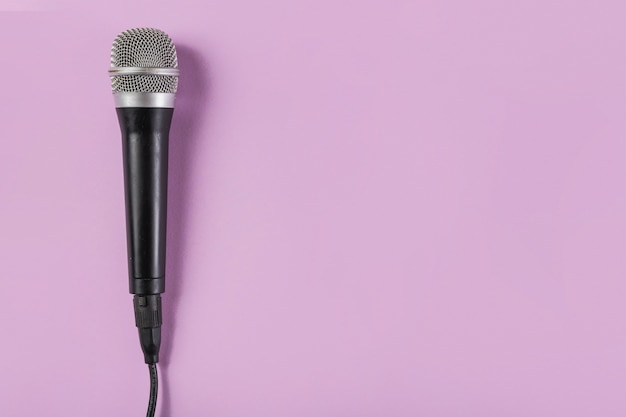Vista superior del micrófono sobre fondo rosa