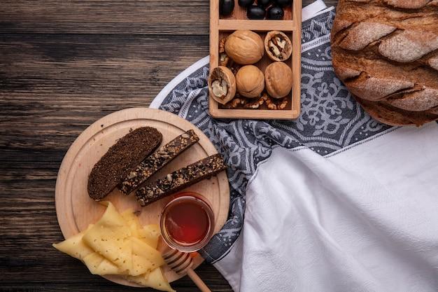 Vista superior de la miel en un tarro con pan negro y queso en un soporte con nueces sobre un fondo de madera