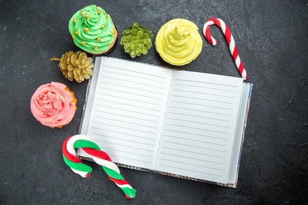 Vista superior de mini cupcakes coloridos, un cuaderno, dulces de navidad y adornos en una superficie oscura.