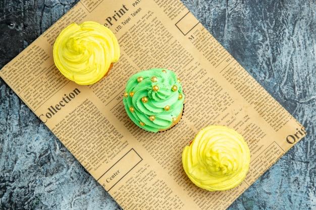Vista superior de mini cupcakes en periódico sobre superficie oscura