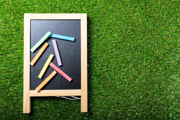 Vista superior de mini pizarra y colores en la pared de hierba de plástico. concepto de regreso a la escuela