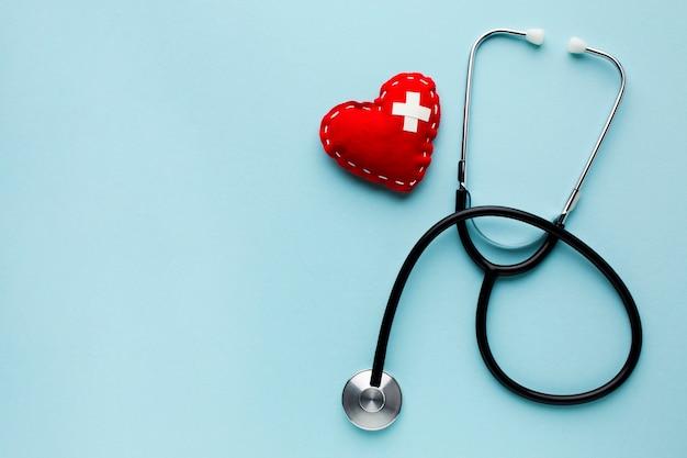 Vista superior minimalista corazón rojo con estetoscopio