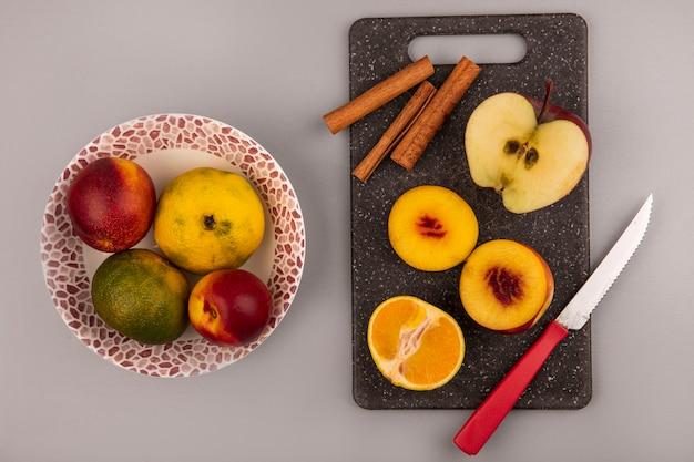 Vista superior de la mitad de melocotones frescos en un tablero de cocina negro con mandarina y manzana con cuchillo con melocotones y mandarinas en un recipiente sobre un fondo gris