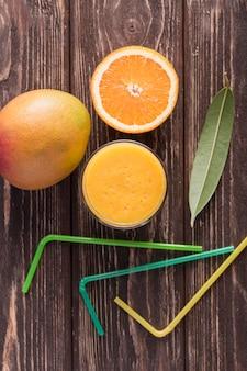 Vista superior de la mitad de naranja y batido de mango