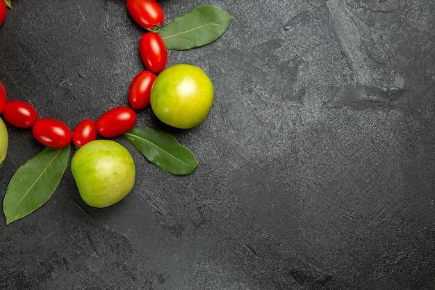 Vista superior de la mitad de los tomates cherry tomates verdes y hojas de laurel sobre suelo oscuro