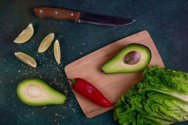 Vista superior mitades de aguacate en una pizarra con lechuga pimiento rojo limón y cuchillo sobre un fondo verde oscuro