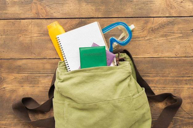 Vista superior mochila con cuaderno en blanco y accesorios de viajero sobre fondo de madera concepto de viaje