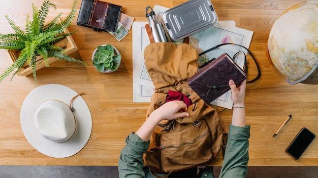 Vista superior de la mochila de embalaje de mujer joven para vacaciones de viaje, concepto de viaje de escritorio.