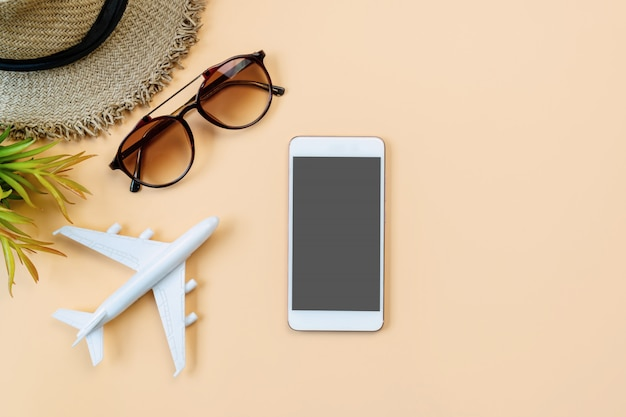 Vista superior del modelo de avión, gafas de sol y sombrero de paja sobre fondo de color naranja