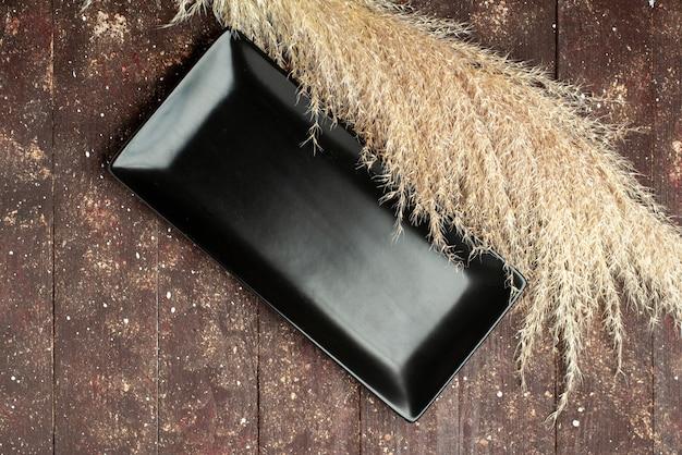 Vista superior del molde de pastel negro vacío en marrón rústico, pastel de madera de madera
