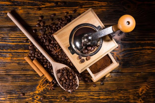 Vista superior del molinillo de café lleno de granos terminados en el cajón, cuchara de madera y dos palitos de canela rodeados de frijoles en la mesa