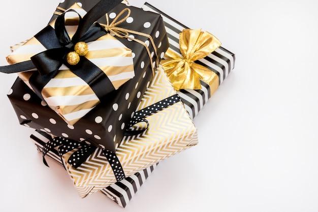 Vista superior de un montón de cajas de regalo en varios colores negro, blanco y dorado.