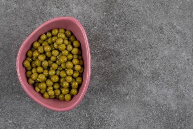 Vista superior. montón de guisantes verdes en tazón de fuente rosa