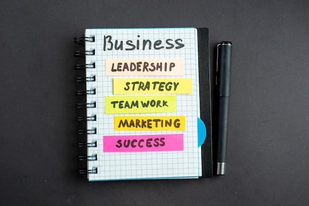 Vista superior motivación notas comerciales con bolígrafo sobre fondo oscuro marketing empresarial trabajo éxito estrategia laboral trabajo en equipo liderazgo de la oficina