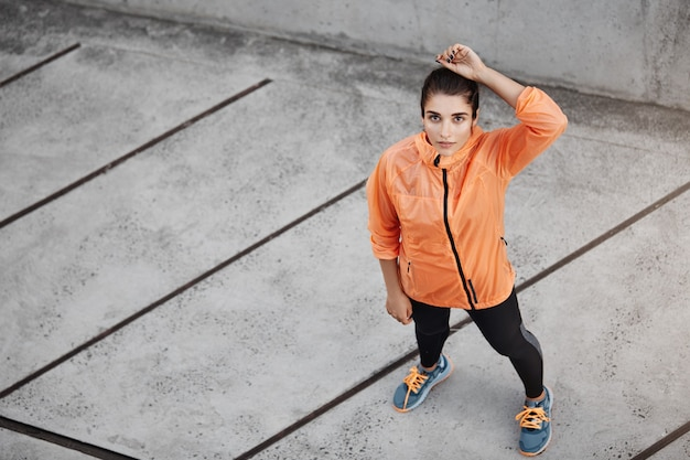 Vista superior motivado confiado joven morena en naranja ru