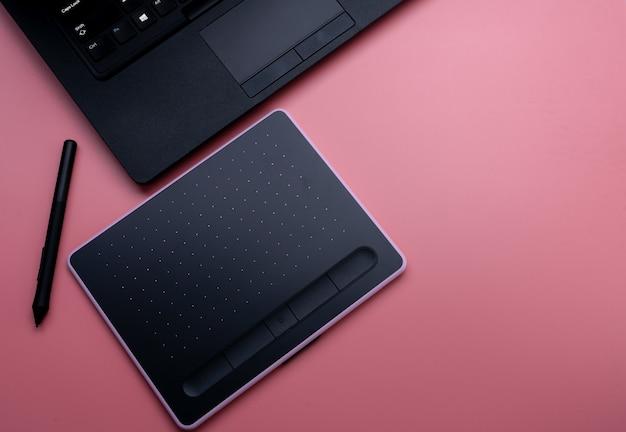 Vista superior del mouse negro, tableta digital y computadora portátil para trabajos de diseño gráfico sobre fondo rosa. vista superior de la tableta gráfica de lápiz. gadget para diseñador gráfico. bluetooth y dispositivo inalámbrico.