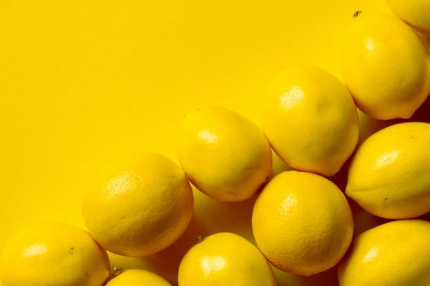 Vista superior de muchos limones maduros sobre una superficie amarilla, fondo o concepto