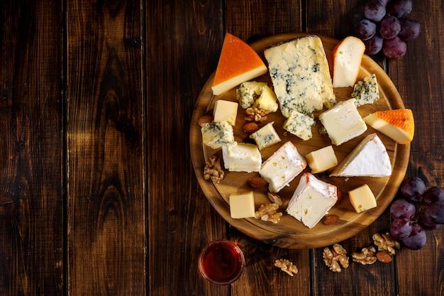 Vista superior de muchos tipos de queso servido sobre tabla de madera