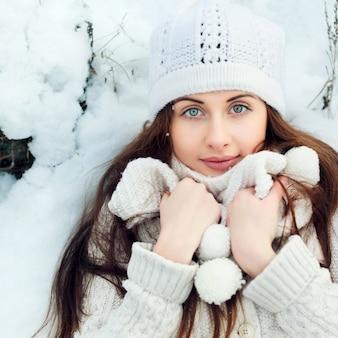 Vista superior de mujer abrigada tumbada en el suelo nevado