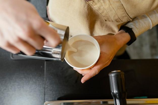 Vista superior de la mujer barista vertiendo leche espumosa en taza