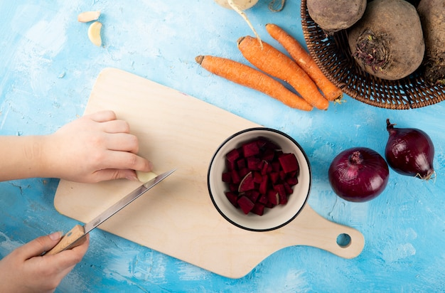 Vista superior mujer corta el ajo en un tablero con remolacha picada en una taza con zanahorias y cebollas rojas sobre una mesa