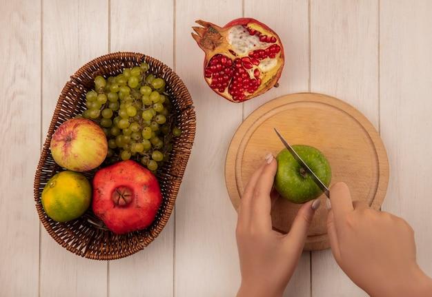 Vista superior mujer corta manzana verde en tabla de cortar con granadas manzanas y uvas en canasta en pared blanca