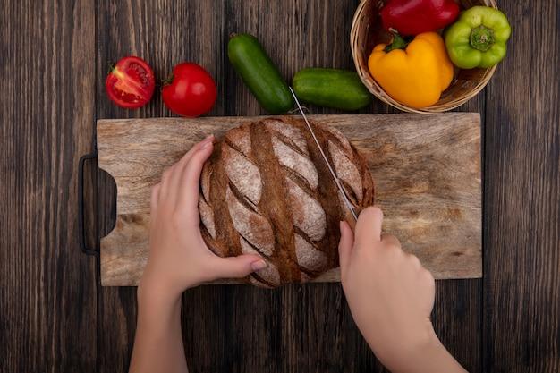 Vista superior mujer corta pan negro en un soporte con tomates, pepinos y pimientos sobre un fondo de madera